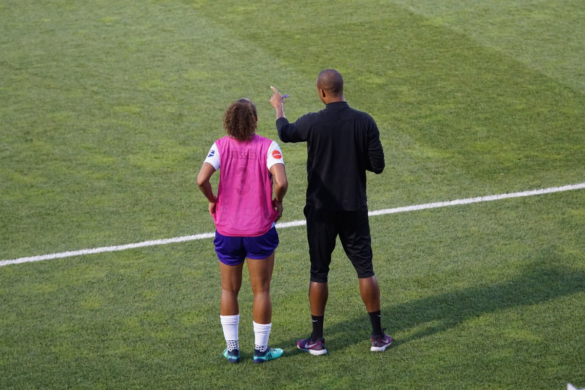 A soccer player and her coach look out at the field