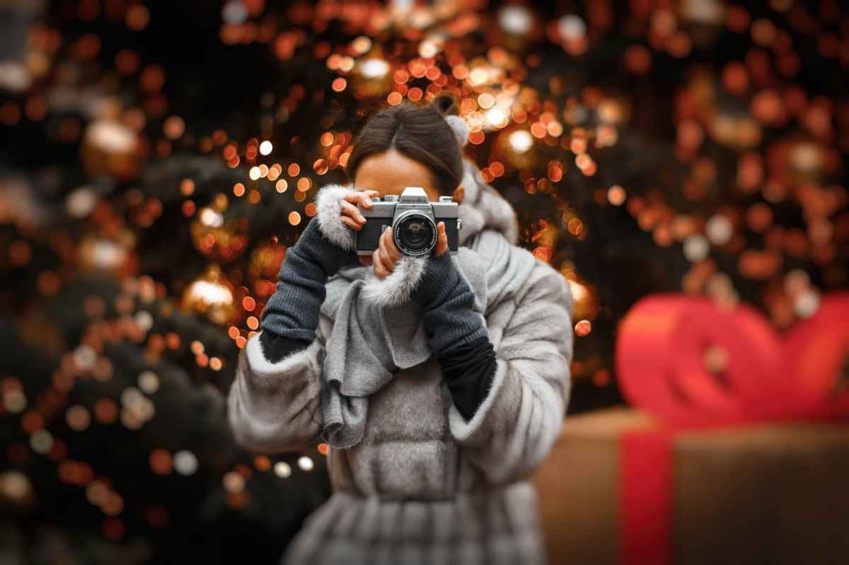 A woman looking at the photographer through a camera