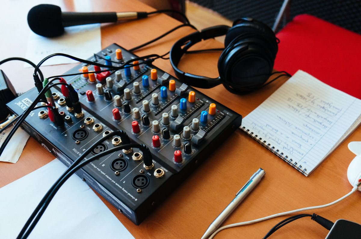 A small audio mixing board, headphones, and a microphone sitting on a desk