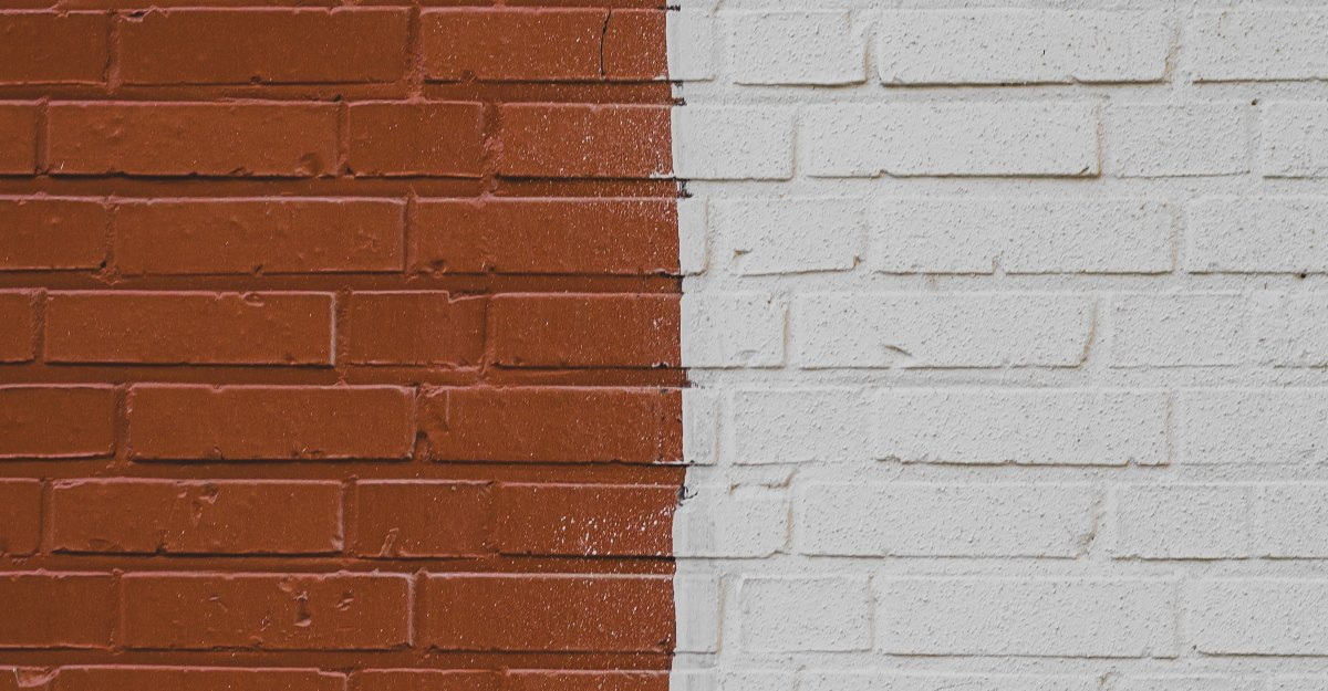 A brick wall painted white on the right and a reddish brown on the left