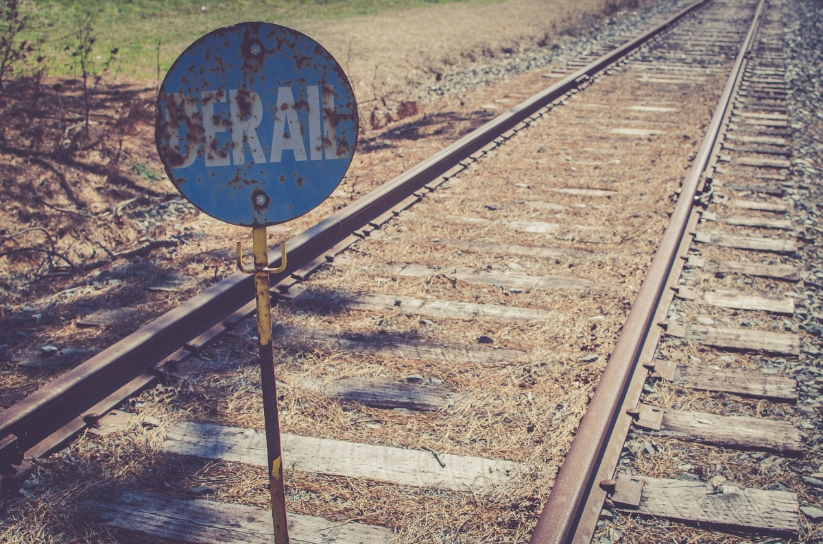 "A rusted sign reading ""Derail"" by railroad tracks"