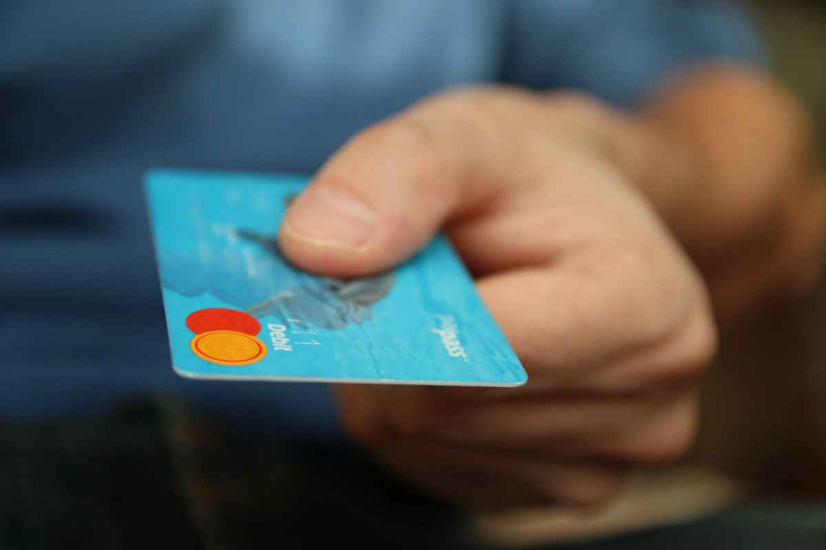 A closeup of a person's hand holding out a debit card