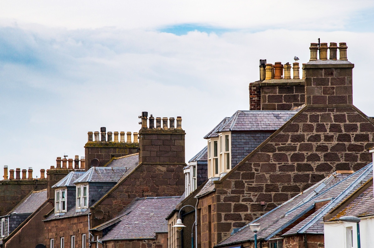 Rooftops of houses with chimney pots and gabled windows