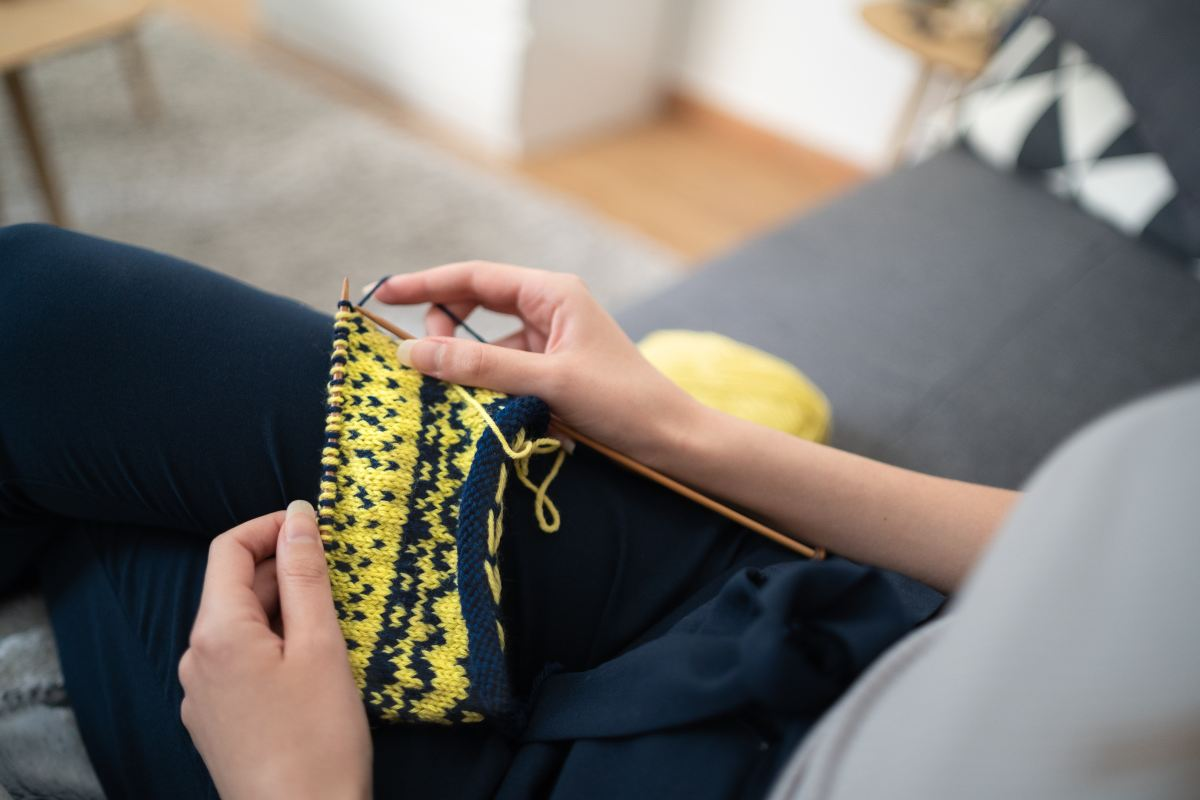 Torso and legs of a person sitting on a couch with a knitting project held in their hands