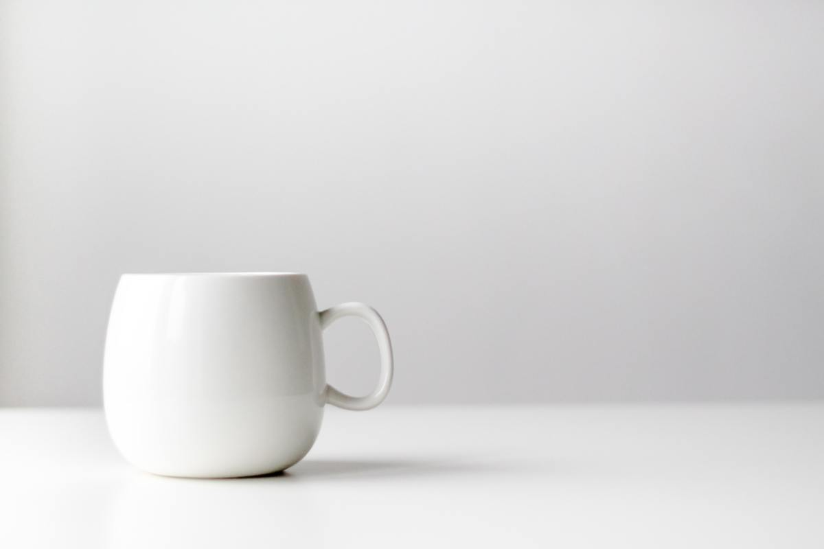A white coffee mug on a white countertop with a white background